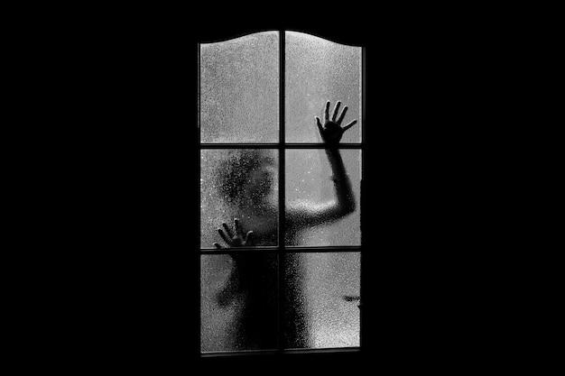 Dunkle silhouette des mädchens hinter glas. allein im raum hinter der tür an halloween in graustufen eingesperrt. albtraum eines kindes mit außerirdischen, monstern und geistern. das böse zu hause in schwarzweiß. im spukhaus.