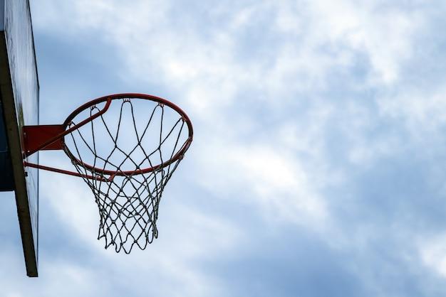 Dunkle silhouette des straßenbasketballreifens an einem wolkigen tag.