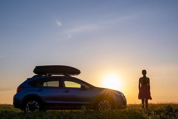 Dunkle silhouette einer einsamen frau, die sich in der nähe ihres autos auf einer grasbewachsenen wiese entspannt und den blick auf den farbenfrohen sonnenaufgang genießt. junge fahrerin, die während der fahrt neben dem suv-fahrzeug ruht.
