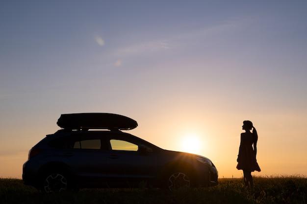 Dunkle silhouette einer einsamen frau, die sich in der nähe ihres autos auf einer grasbewachsenen wiese entspannt und den blick auf den farbenfrohen sonnenaufgang genießt.