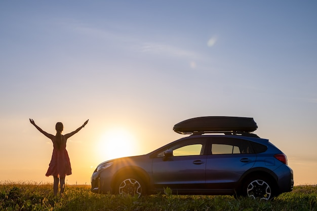 Dunkle silhouette einer einsamen frau, die sich in der nähe ihres autos auf einer grasbewachsenen wiese entspannt