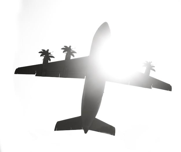Dunkle silhouette eines flugzeugs auf himmelshintergrund mit sonnenlicht, ansicht von unten.
