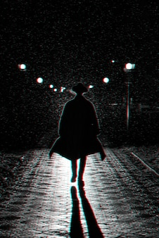 Dunkle silhouette eines mannes in einem mantel und in einem hut im regen auf einer nachtstraße. schwarzweiß mit 3d-glitch-virtual-reality-effekt