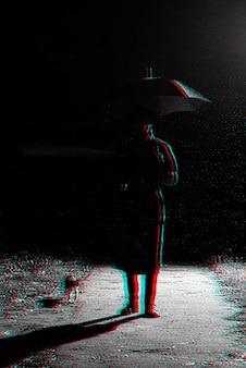 Dunkle silhouette eines mannes in einem regenmantel und einem hut unter einem regenschirm auf der straße im regen. schwarzweiß mit 3d-glitch-virtual-reality-effekt