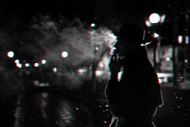 Dunkle silhouette eines mannes mit hut rauchen einer zigarette im regen auf einer nachtstraße. schwarzweiß mit 3d-glitch-virtual-reality-effekt