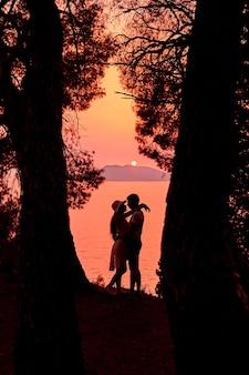 Dunkle silhouette eines umarmenden paares verliebt in der nähe des meeres