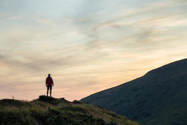 Dunkle silhouette eines wanderers auf einem berg bei sonnenuntergang, der auf gipfel wie ein gewinner steht.