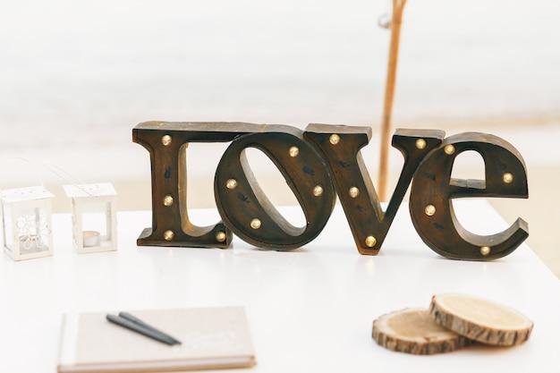 Dunkle stahl schriftzug liebe mit lampen steht auf weißem tisch