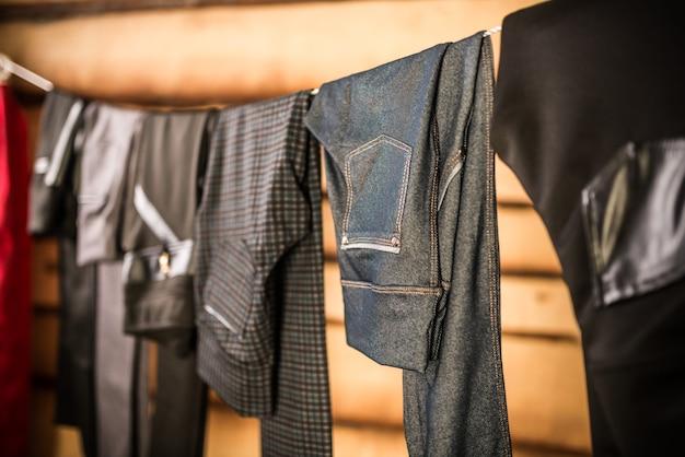 Dunkle, stilvolle damenhosen und jeans hängen an einem seil im kleiderschrank. das konzept, kleidung für jeden tag auszuwählen. stilvolles damenbekleidungskonzept