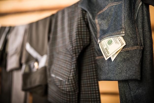 Dunkle, stilvolle damenhosen und -jeans hängen an einem seil im kleiderschrank, und geldscheine fallen aus ihren taschen. das konzept, kleidung für jeden tag auszuwählen. taschengeldkonzept