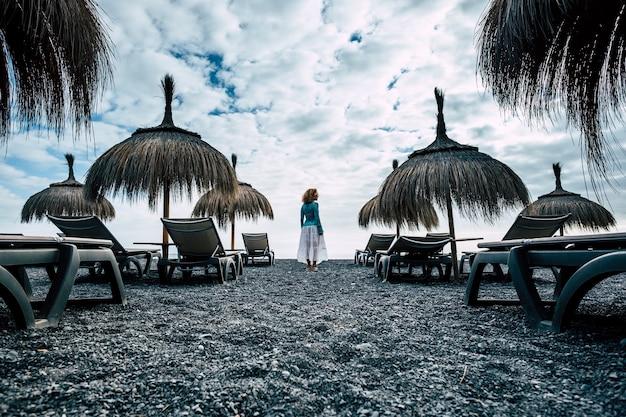 Dunkle und blaue farben und töne für episches bild mit schönem kaukasischem mittelaltermodell am strand im winterwetter. kaltes und schönes kleid und körper stehen alleine mit erstaunlicher wolkenoberfläche auf