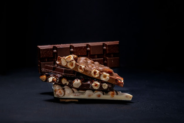 Dunkle und weiße schokolade mit haselnüssen auf einem schwarzen hintergrund.