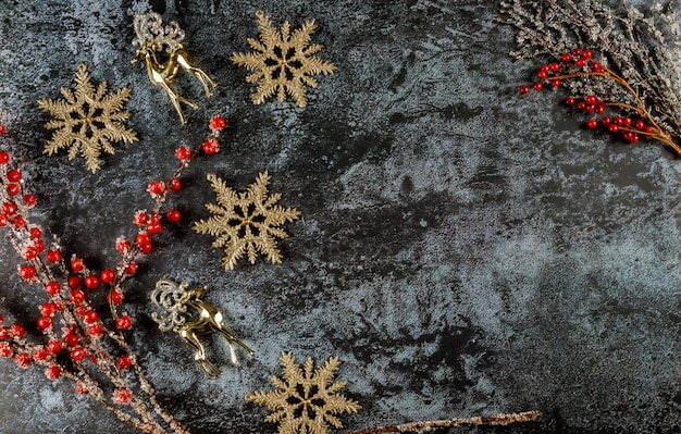 Dunkle weihnachtsfläche mit rentier-, schneeflocken- und roten beerenzweig