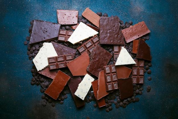 Dunkle, weiße und milchschokoladenstücke. ansicht von oben