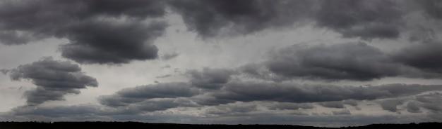 Dunkle wolken am grauen himmel, ein düsteres wetterpanorama bis zum horizont.