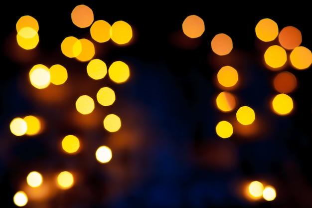 Dunkler abstrakter gold-bokeh schein auf schwarzem hintergrund. weihnachtsgoldene lichter.