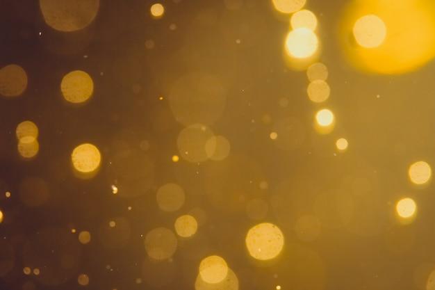 Dunkler abstrakter gold-bokeh schein auf schwarzem hintergrund