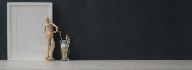 Dunkler arbeitsbereich des modernen künstlers mit modellrahmen und malerei mit kopierraum