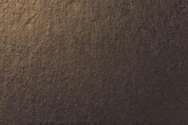 Dunkler bronzehintergrund des natürlichen schiefers. textur aus braunem stein