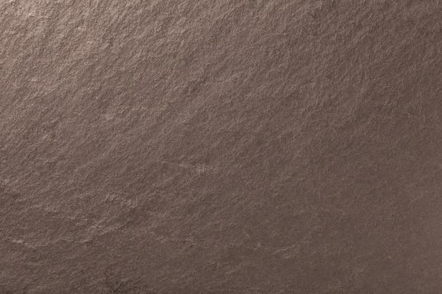 Dunkler bronzehintergrund des natürlichen schiefers. textur aus stein