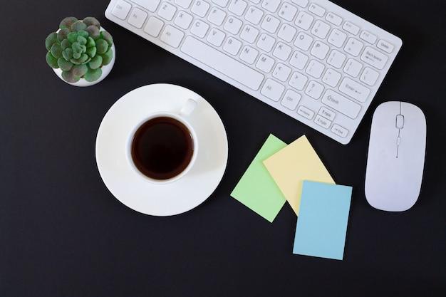 Dunkler bürotisch mit tastatur, pflanze, tasse kaffee und aufklebern draufsicht. kopieren sie platz für ihren text