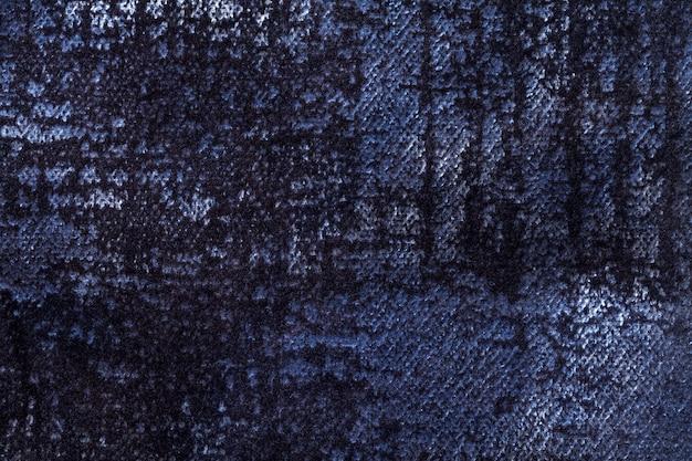 Dunkler dunkelblauer hintergrund des weichen, flauschigen stoffes. textur aus indigo-samt-textil