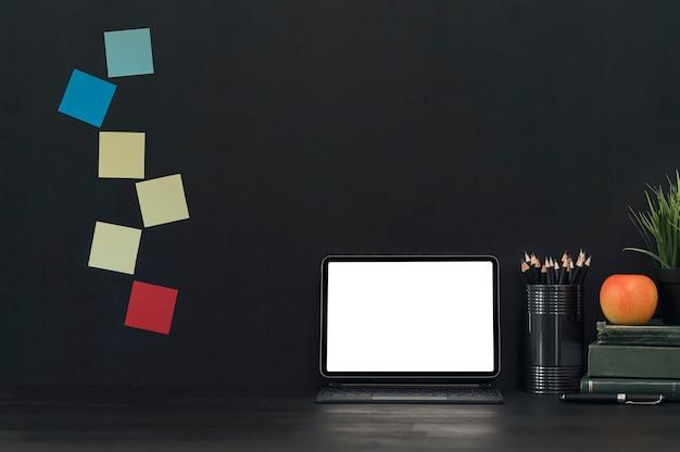 Dunkler farbarbeitsbereich mit tablett mit leerem bildschirm, tastatur und stationär auf schwarzem tisch.