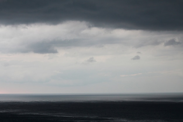 Dunkler himmel und dramatische schwarze wolke vor regen. regen kommt in den strand