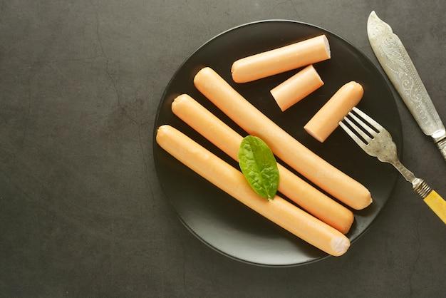 Dunkler hintergrund des rohen hühnerfleisch-hotdogwurstfrühstücks