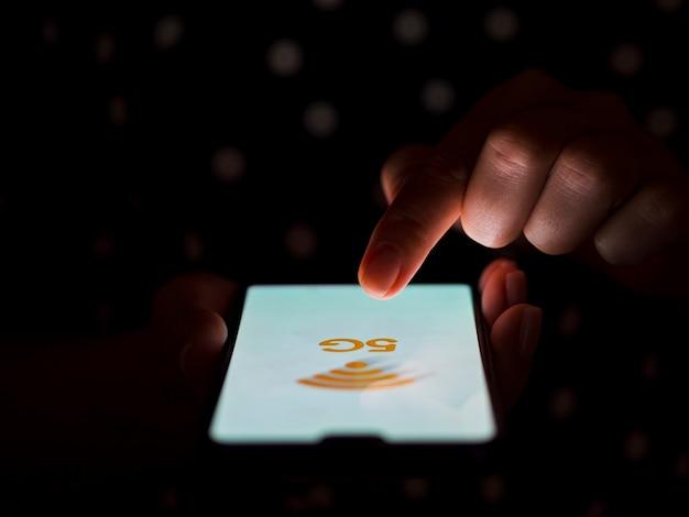Dunkler hintergrund des rührenden telefonbildschirms des fingers