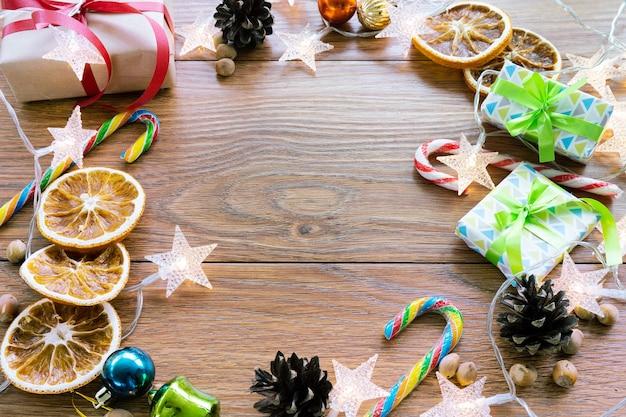 Dunkler hintergrund des weihnachtsneujahrs mit festlicher verzierung und geschenkboxen, süßigkeiten, orange, zapfen, weihnachtsspielzeug. neujahrsfeiertag, das konzept der feier.