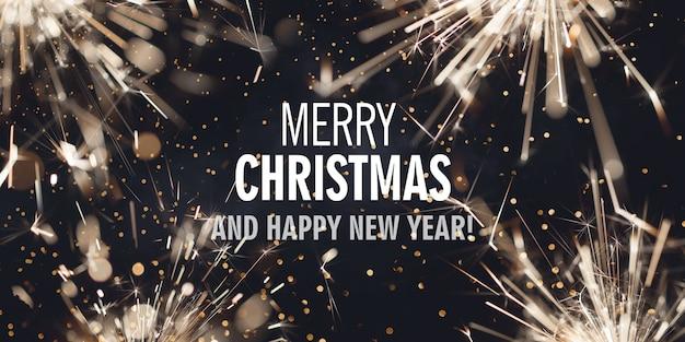 Dunkler hintergrund mit brennenden wunderkerzen und text frohe weihnachten und ein gutes neues jahr