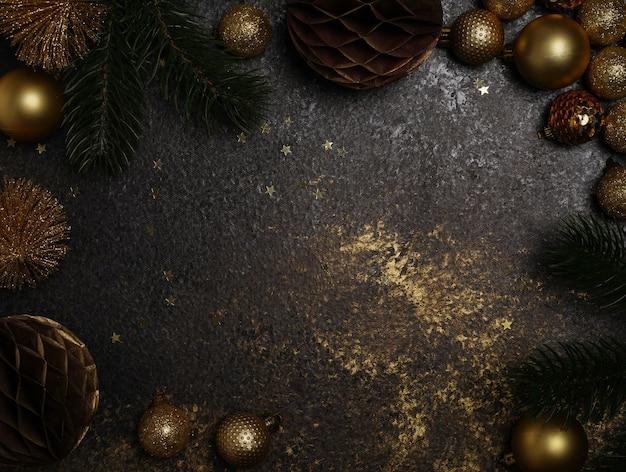 Dunkler hintergrund mit goldenen, goldenen weihnachtsdekorationen und sternen, ein ort für text oder neujahrsgrüße. foto in hoher qualität