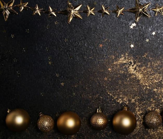Dunkler hintergrund mit goldenen weihnachtsdekorationen und sternen ein platz für text oder neujahrsgrüße