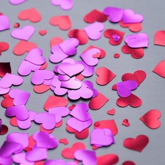 Dunkler hintergrund mit roten und purpurroten herzkonfettis für valentinstag.