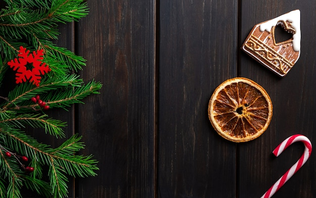 Dunkler hölzerner hintergrund mit weihnachtsdekorationen und tannenbaum