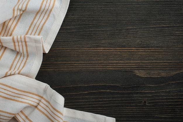 Dunkler hölzerner hintergrund mit weißer serviette