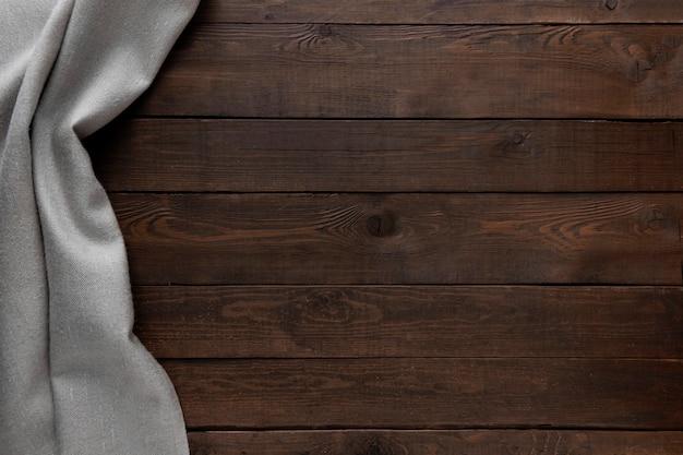 Dunkler holzhintergrund mit grauer tischdecke.