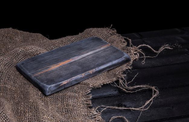 Dunkler holztisch für produkt, alter schwarzer hölzerner perspektiveninnenraum mit altem schneidebrett