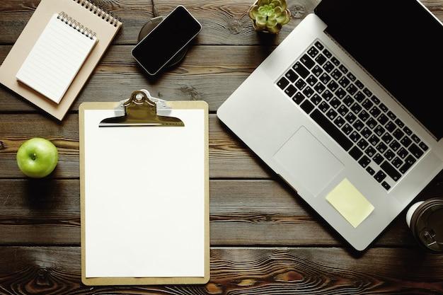 Dunkler holztisch mit laptop, draufsicht des notizblockes