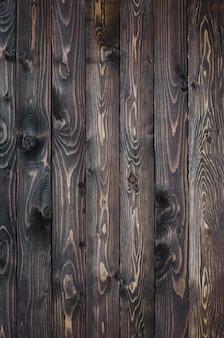 Dunkler holzuntergrund aus schmalem brett, dunkelbraun lackiert.
