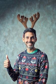 Dunkler kerl mit kurzem grauem bart, der in blauem weihnachtspullover und rentiergeweih-stirnband lächelt