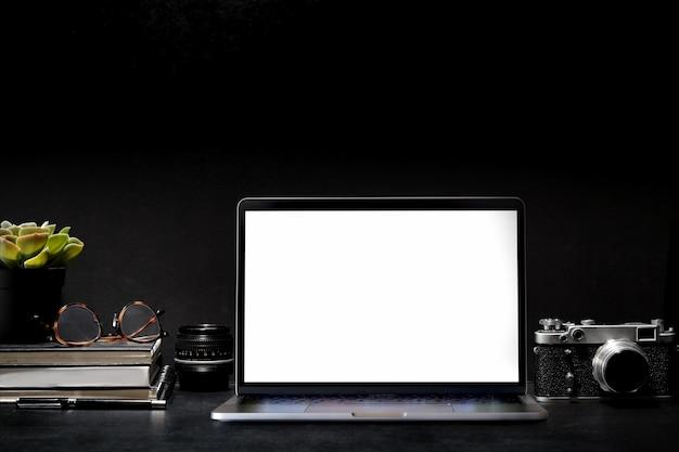 Dunkler kreativer fotografschreibtisch mit weinlesekamera, linse und laptop des leeren bildschirms
