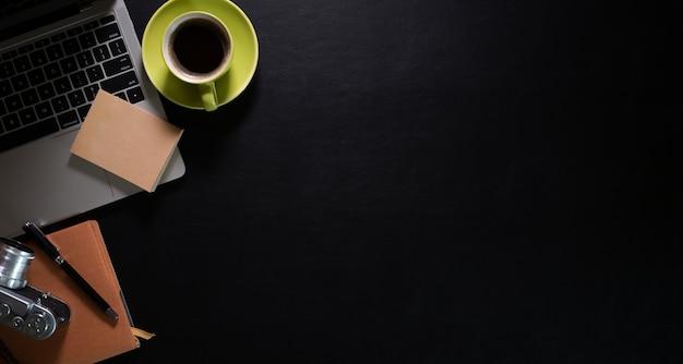 Dunkler lederner arbeitsplatz des schreibtischs mit schwarzem tasse kaffee-, laptop- und kopienraum