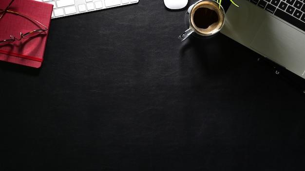 Dunkler lederner schreibtisch des büros mit computer und versorgungen. draufsicht mit kopienraum