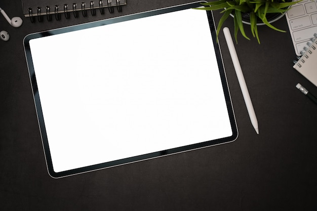 Dunkler lederner schreibtisch des büros mit modelltablette des leeren bildschirms