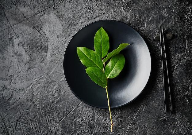 Dunkler leerer teller mit asiatischem essen mit schwarzen stäbchen auf schwarzem schieferbrett. asiatische art des essens.