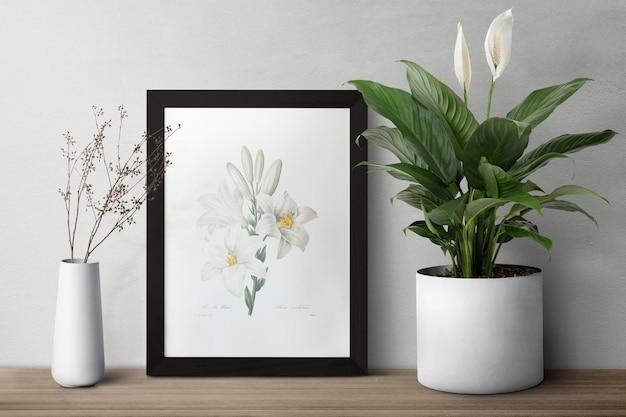 Dunkler moderner bilderrahmen auf einem regal mit pflanzen