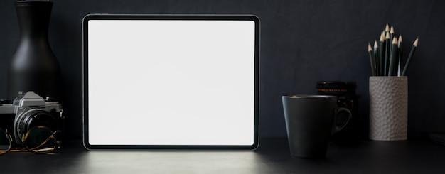 Dunkler moderner schreibtisch mit tablett mit leerem bildschirm, becher, kamera, dekoration und anderem zubehör