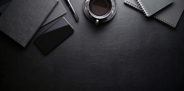 Dunkler modischer arbeitsplatz mit smartphone und büroartikel auf schwarzer ledertabelle